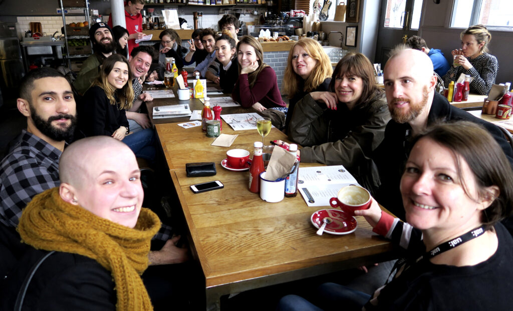 Group of smiling students at cafe in the northern part of London on the website A Better Version